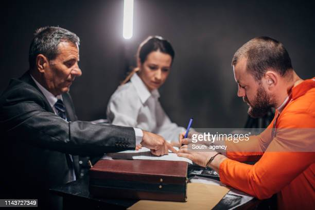 man with handcuffs signing document in interrogation room - confession law stock pictures, royalty-free photos & images