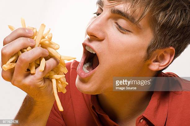 man with handful of fries - handful stock pictures, royalty-free photos & images