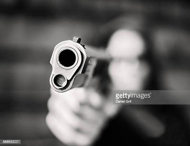 Man with handgun pointing towards camera