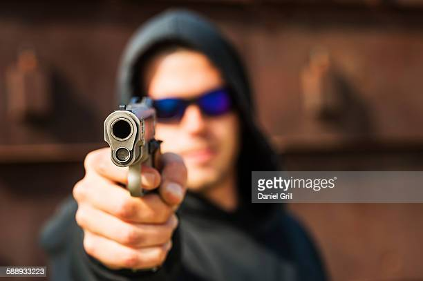 man with handgun pointing towards camera - aiming stock pictures, royalty-free photos & images