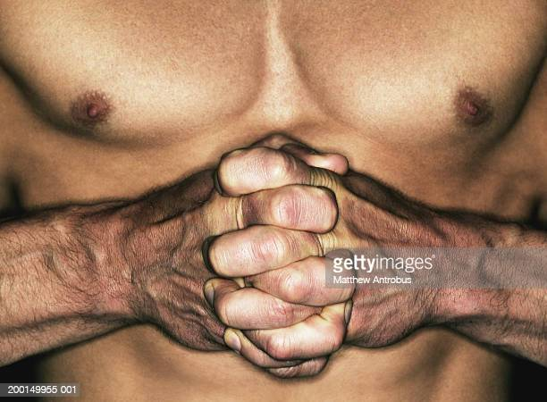 Man with hands clasped around bare chested man, close-up