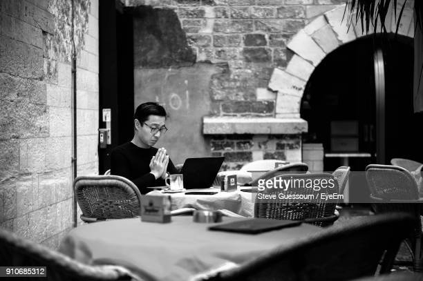 Man With Hands Clasped Using Laptop While Sitting At Table In Cafe