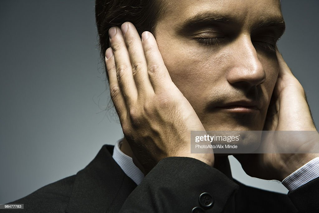 Man with hands held over ears and eyes closed : Stock Photo