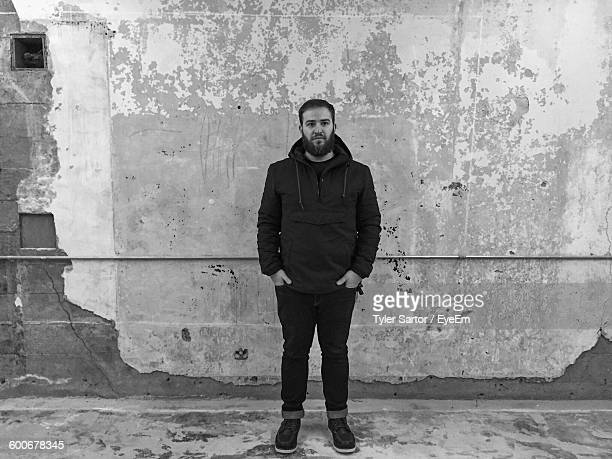Man With Hands In Pockets Standing Against Wall