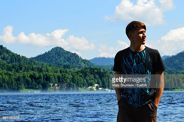 Man With Hands In Pockets Standing By Lake Against Sky