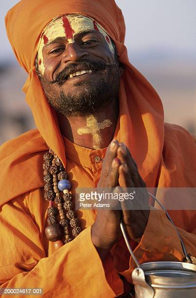 man with hands in prayer position, smiling, portrait - peter adams stock pictures, royalty-free photos & images