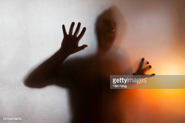 Man with hands pressed up against glass behind translucent facade