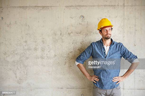 man with hard hat at concrete wall thinking - hand on hip stock pictures, royalty-free photos & images