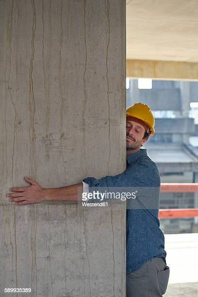 Man with hard hat embracing concrete pillar on construction site