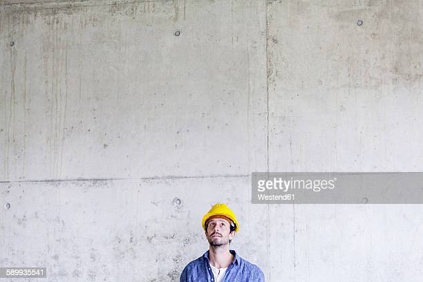 Man with hard hat on construction site at concrete wall looking up