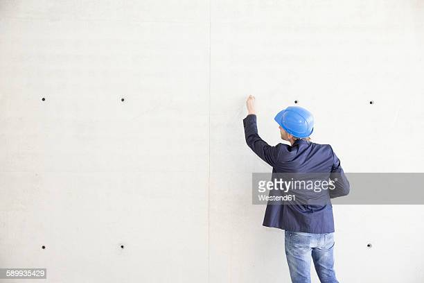 Man with hard hat on construction site drawing on concrete wall