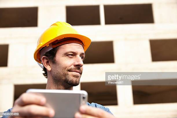 Man with hard hat on construction site holding cell phone