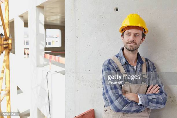 Man with hard hat on construction site thinking
