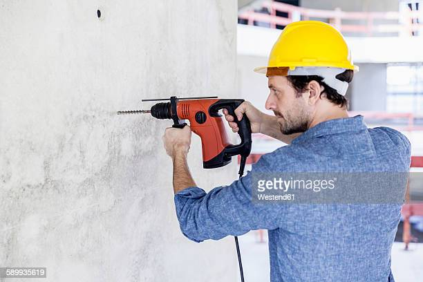 Man with hard hat on construction site using drill