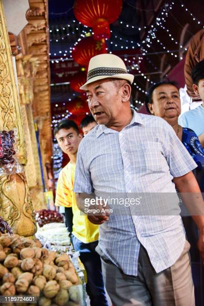 man with hat at a night market in urumqi - sergio amiti stock pictures, royalty-free photos & images