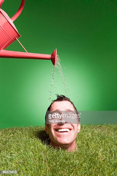 man with head coming out of grass getting watered