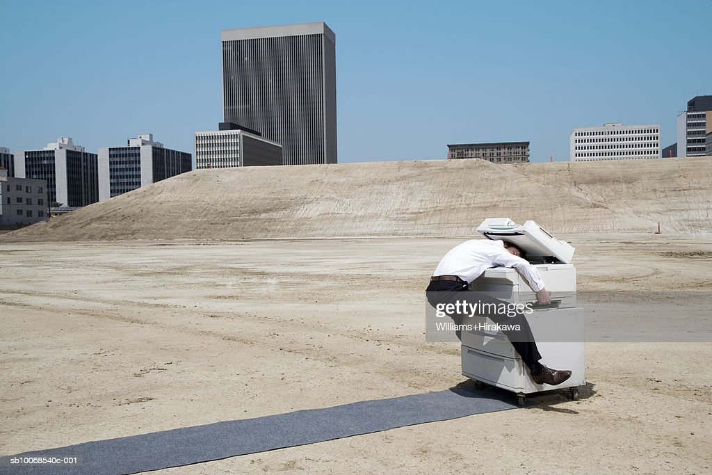 Man with head in copy machine on construction site, side view : Stock Photo