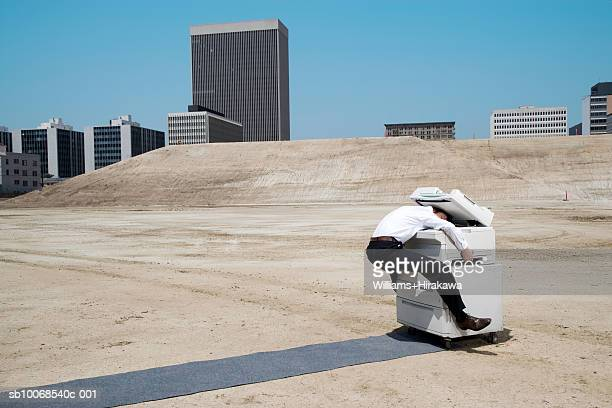 Man with head in copy machine on construction site, side view