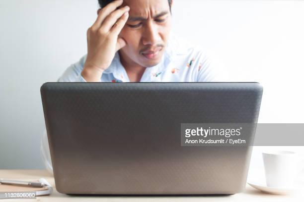 Man With Head In Hands Looking At Laptop Against Wall