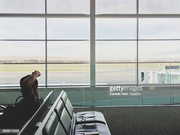 man with head in hands sitting in airport lobby - danielle reid stock pictures, royalty-free photos & images