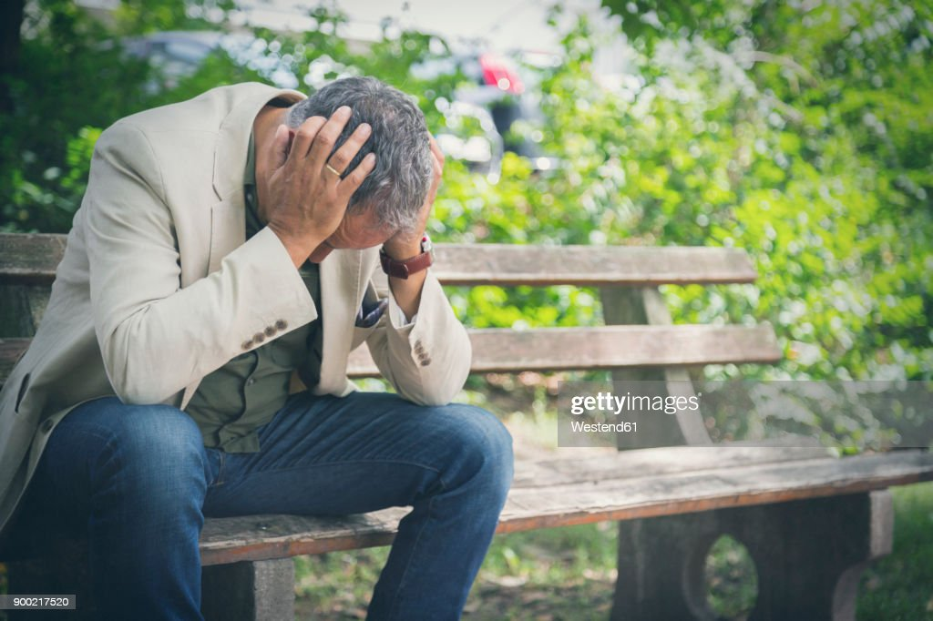 Man with head in his hands sitting on park bench : Stock Photo