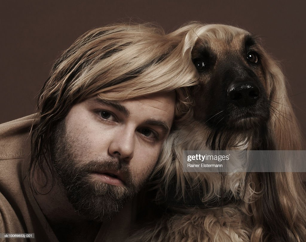 Man with head under Afgan Hound's ear, portrait, studio shot : Stockfoto