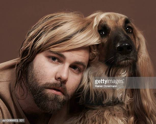 man with head under afgan hound's ear, portrait, studio shot - pair stock pictures, royalty-free photos & images