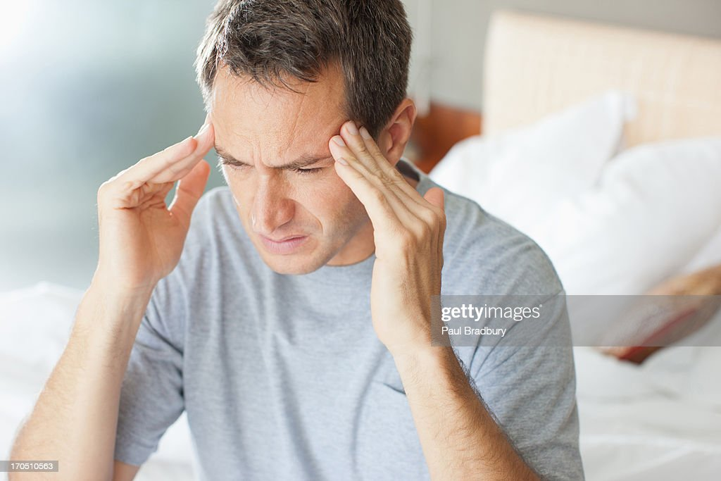 Man with headache rubbing forehead : Stock Photo