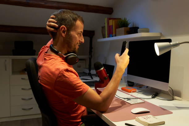 Man with headphone text messaging on smart phone while working from home