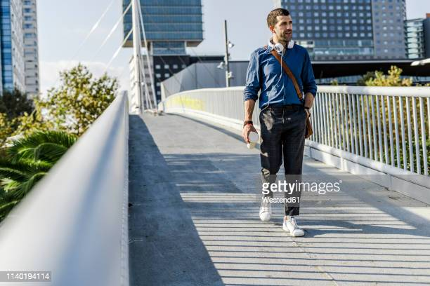 man with headphones and coffee to go walking on a footbridge - adulto de idade mediana - fotografias e filmes do acervo