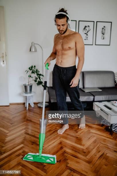 mann mit kopfhörer-reinigung haus und musik hören - halbbekleidet stock-fotos und bilder