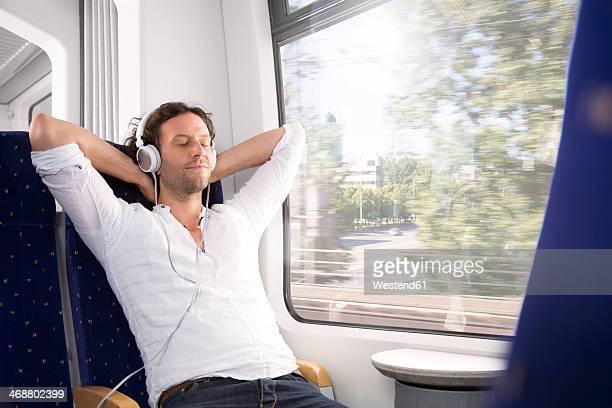 man with headphones in a train - hände hinter dem kopf stock-fotos und bilder