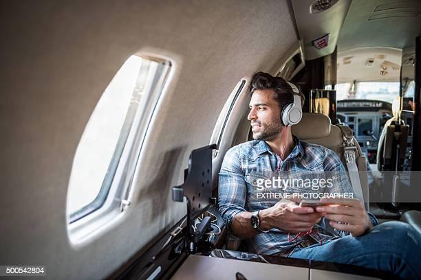 男性、ヘッドフォンにプライベートジェット飛行機