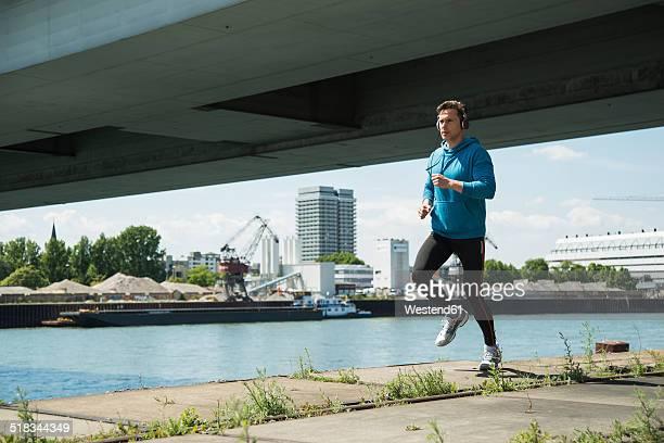 Man with headphones jogging at riverside