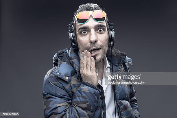 Man with headphones looking surprised at camera