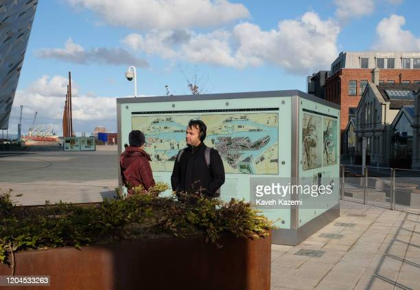 A man with headphones on his ears stands outside the Titanic Belfast Museum where a map of the site is seen behind him on October 30 2019 in Belfast...