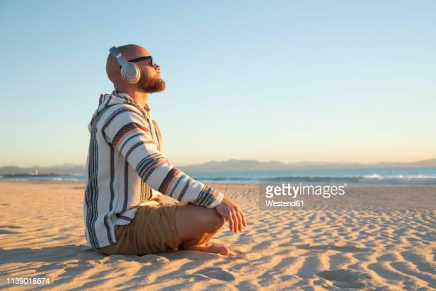 man with headphones sitting at the beach - hoodie headphones stock pictures, royalty-free photos & images