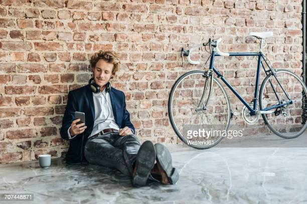 Man with headphones sitting on floor looking at cell phone