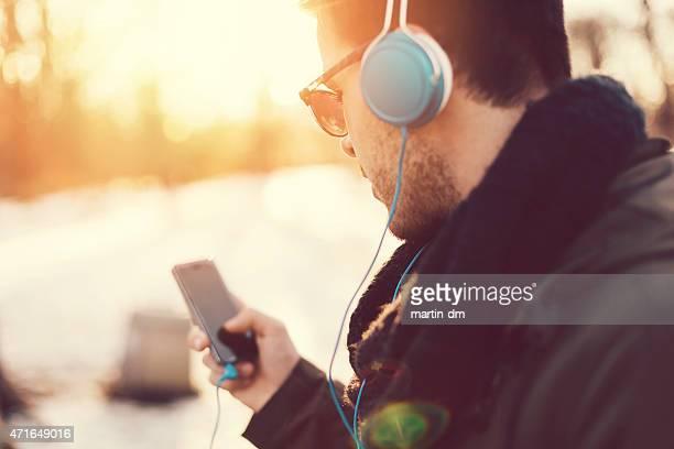 Homme avec un casque à envoyer des SMS sur smartphone