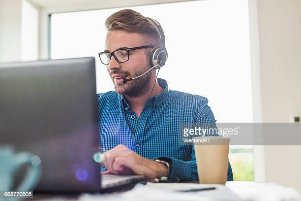 Man with headset and laptop in office