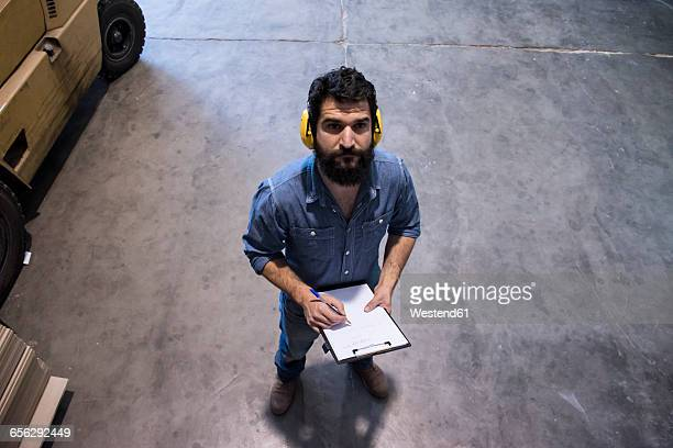 Man with hearing protection making notes in a folder in a warehouse of a factory