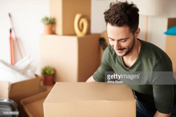 Man with heavy cardboard box. Debica, Poland