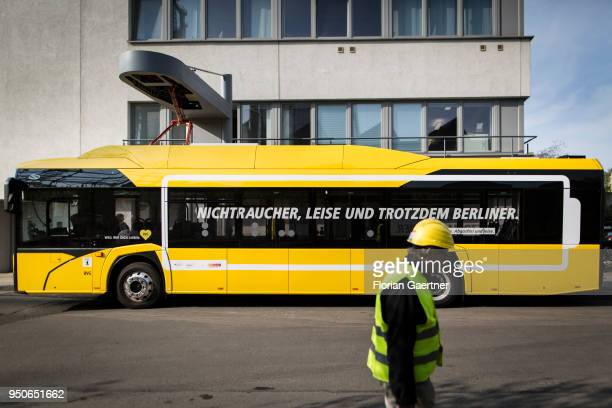 A man with helmet walks in front of a charging electric bus on April 24 2018 in Berlin Deutschland