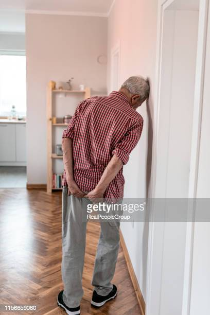 Man with hemorrhoids holding his ass in pain