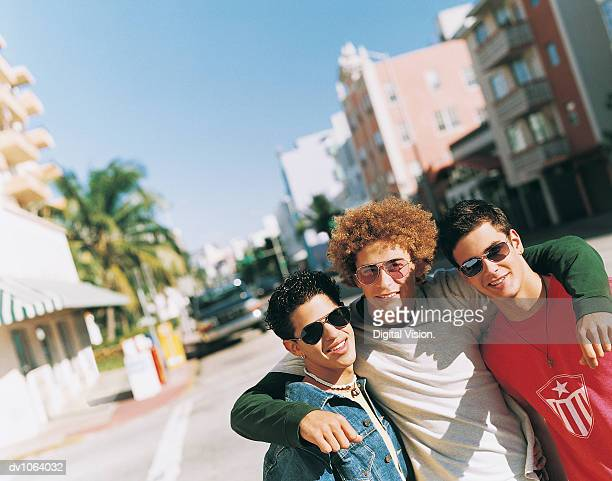 Man With His Arm Around His Two Friends Standing on an Urban Road