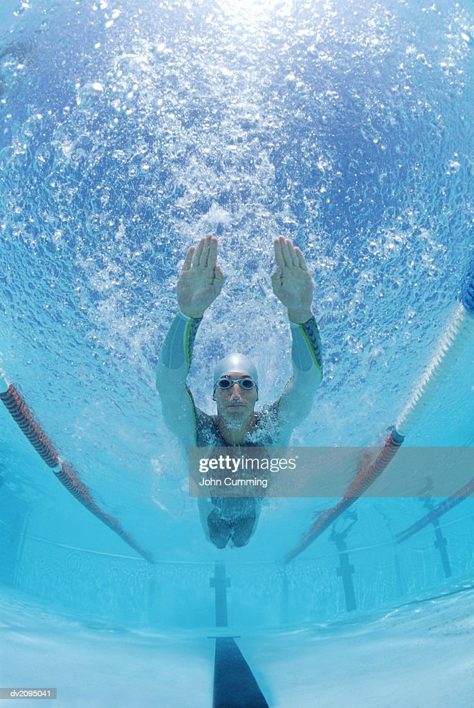 Man With His Arms Stretched Out Underwater in a Swimming Pool : Stock Photo