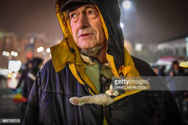 Man with his cat takes part in an anti-governmental demonstration in front of the Romanian government headquarters in Bucharest on Romania's National...