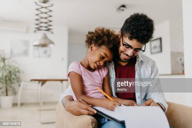man with his child is doing finances at home. - fun calculator stock photos and pictures
