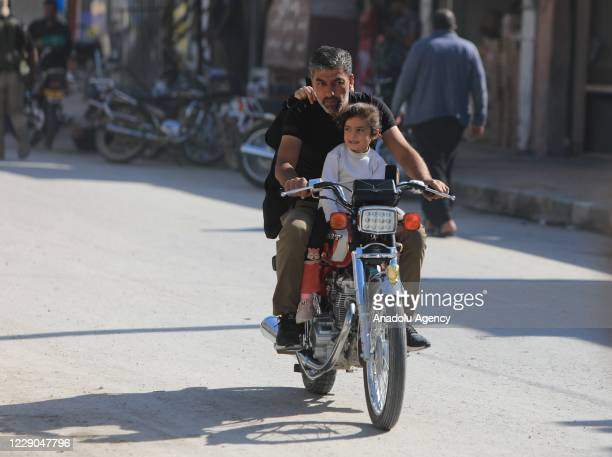 A man with his child rides a motorbike on the first year of Operation Peace Spring as life turned to normal in Tal Abyad Syria on October 13 2020 A...