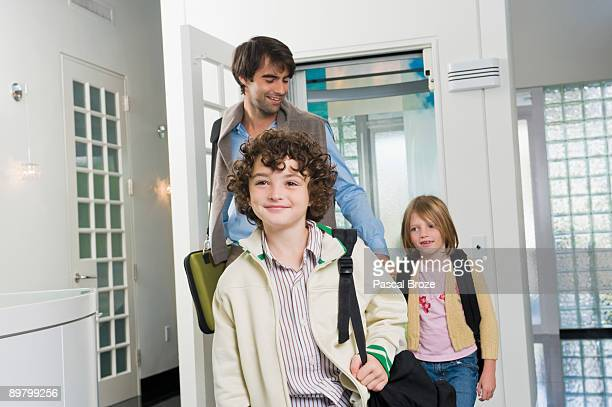 Man with his children entering a house